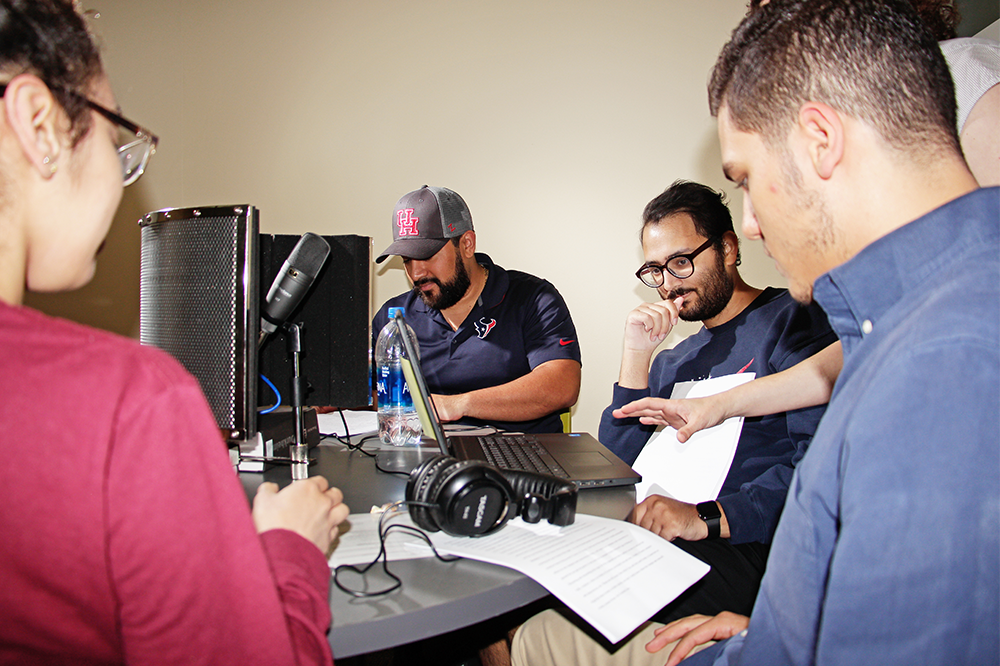 photo students sitting around a table recording a podcast
